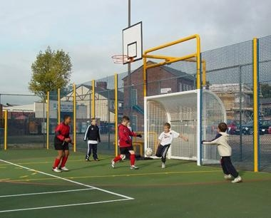 Children playing football in a Steelway MUGA